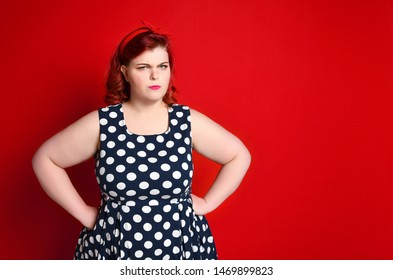 Closeup of a fat angry redhead woman holding her cheek by hand. pinup girl isolated on retro vintage 50s style.