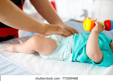 Close-up of father changing diaper of his newborn baby daughter. Little child, girl on changing table in bathroom with rattle toys.
