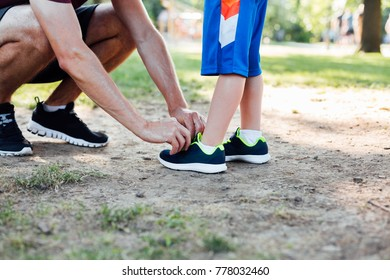 Closeup of father preparing his son for running