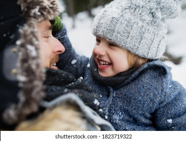 Close-up of father with small son in snowy winter nature, talking in.