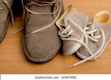 Closeup of father's shoes close to child's shoes on a parquet floor