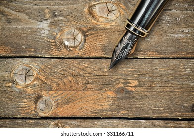 Closeup of the feather of a fountain pen on wooden background