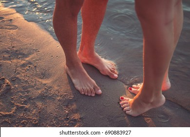 Closeup of feet of a couple in love on a beach, beside water, standing on the sand