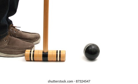 closeup of feet croquet mallet and ball over white