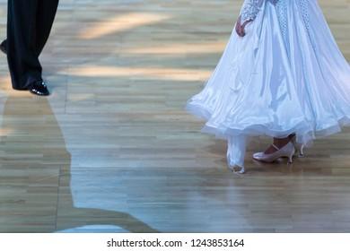 Closeup of Feet and Legs of Professional Ballroom Dance Couple Prior to Performing Youth Standard Program on Dancefloor.Horizontal Shot
