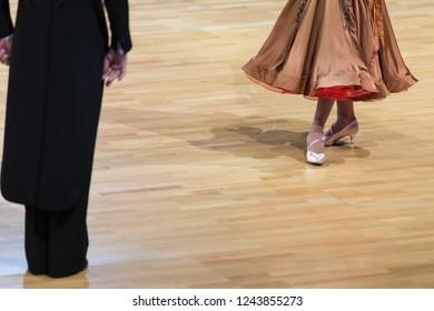 Closeup of Feet and Legs of Professional Ballroom Dance Couple Prior to Performing Youth Standard Program on Dancefloor.Horizontal Image