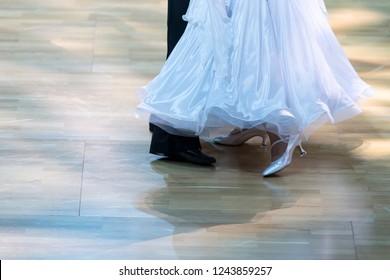 Closeup of Feet and Legs of Professional Ballroom Dance Couple Prior to Performing Youth Standard Program on Dancefloor.Horizontal Image Orientation