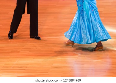 Closeup of Feet and Legs of Professional Ballroom Dance Couple Prior to Performing Youth Standard Program on Dancefloor.Horizontal Image Composition