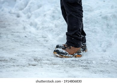 close-up of feet of man with brown leather boots in the snow on side view