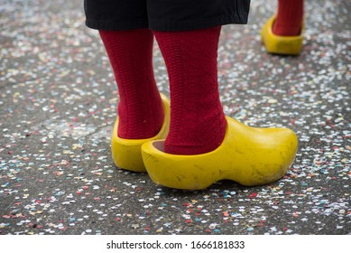 Closeup of feet of man wearing red socks and yellow wooden shoes in the street during the carnival