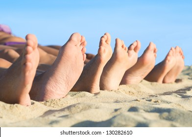 Closeup of feet row lying in line at summer beach