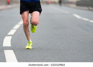 Closeup of the feet of a runner. A man runs along the city road.