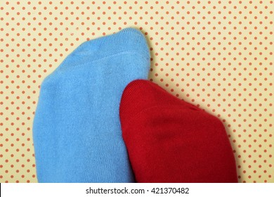closeup of the feet of someone with a blue sock in one foot and a red sock in the other, on a dot patterned background