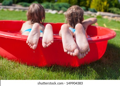 Close-up of feet two sisters in small pool