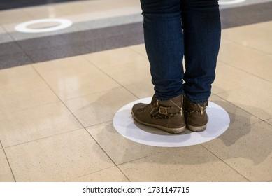 Schließung von Füßen der Frau, die während der Covid-19-Pandemie im Sozialdistanzsymbol auf dem Boden des Bahnhofs steht