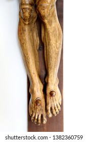 closeup of feet of wooden statue showing jesus christ on the cross