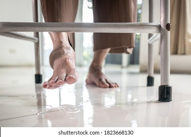 Closeup of the feet,Asian elderly person use a walker to help her walk,water spilled on the ground,careful of slippage,senior woman is stepping on the wet floor,danger,accident,damage of slip and fall