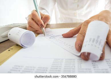Closeup of female accountant looking through the receipts while working on a report.