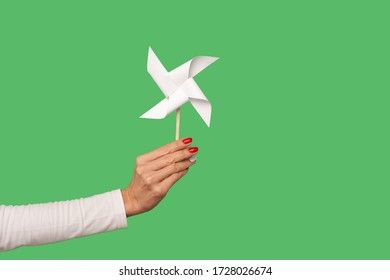 Closeup of female arm holding pinwheel toy on stick, origami hand mill isolated on green background, showing paper windmill, white spinner to play childhood game, party favour. indoor studio shot