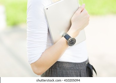 Close-up of female arm wearing a watch and carrying a digital tablet outdoors.