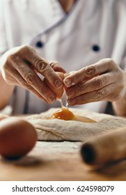 Close-up of female baker hands breaking egg into raw dough. Concept of baking and food preparation.