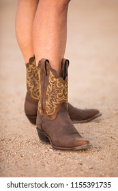 Closeup of female with bare legs in brown cowboy boots standing on a gravel road