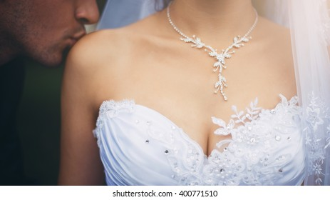 Close-up of female breasts in the low-necked dress and the groom kissing a bride's shoulder. Beautiful necklace around the neck of the bride. Woman has very beautiful shoulders, collarbones, breast.