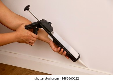 Close-up of a female contractor using a mastic gun to seal a baseboard