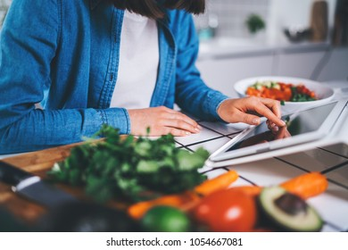 Closeup of female cook using digital tablet device for searching healthy meal recipes, young woman sitting in the kitchen preparing vegetarian food or salad, eating raw food