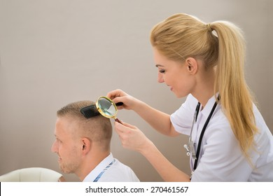 Close-up Female Dermatologist Looking At Patient's Hair Through Magnifying Glass
