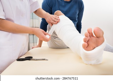 Close-up Of A Female Doctor Bandaging Patient's Leg