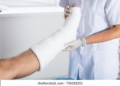 Close-up Of A Female Doctor Examining Injured Person's Leg In Clinic