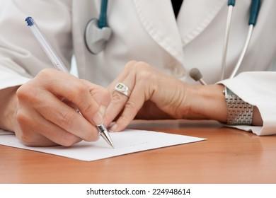 Closeup of female doctor hand writing a medical prescription. Selective focus.