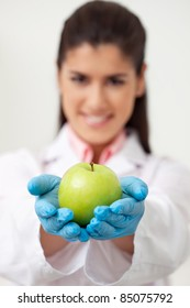 Closeup of female doctor holding a green apple