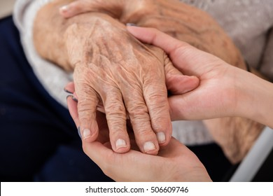 Close-up Of Female Doctor Holding Hand Of Senior Patient