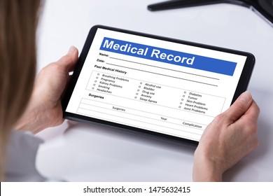 Close-up Of Female Doctor Looking Patient Information Form On Digital Tablet Over Desk