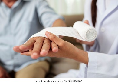 Close-up of female doctor putting a bandage on injured hand of senior man at hospital