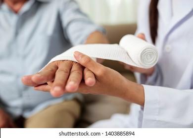 Nahaufnahme eines weiblichen Arztes, der einen Verband auf die verletzte Hand eines älteren Mannes im Krankenhaus auflegt