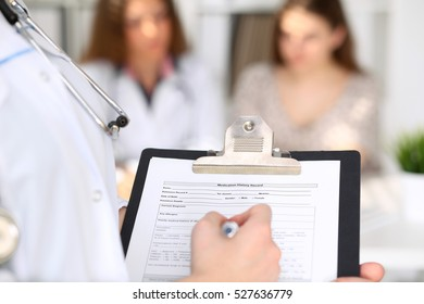 Close-up of a female doctor while filling up medical history record