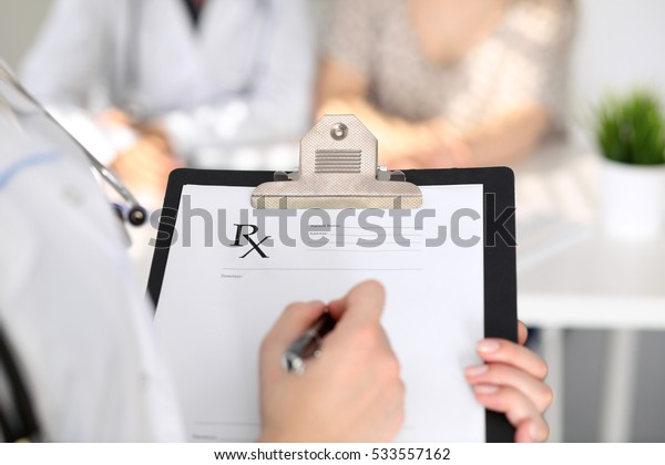 Close-up of a female doctor while filling up medical prescription