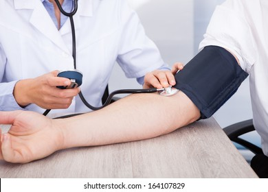 Close-up Of Female Doctor's Hand Checking Blood Pressure