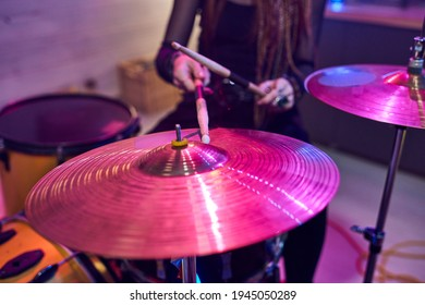 Close-up of female drummer using sticks while playing on drums during performing