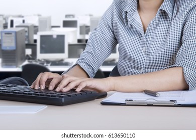 Closeup of a female employee working with a computer and clipboard on the desk while sitting in the office