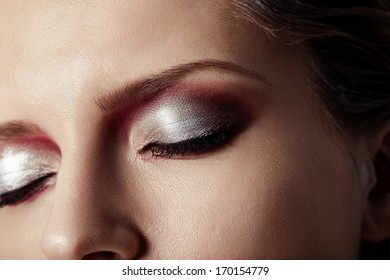 closeup of female eye with beautiful magenta make-up