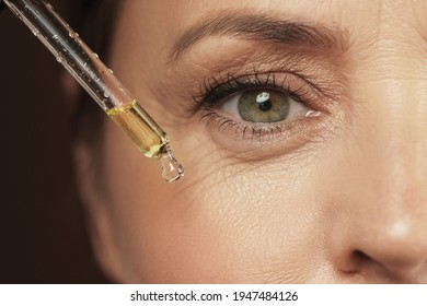 Closeup of female eye and dropper with rejuvenating serum - Shutterstock ID 1947484126