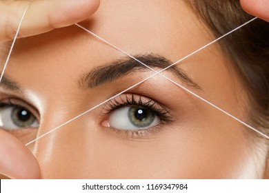Close-up of female eye with a thread. Eyebrow threading - epilation procedure for brow shape correction