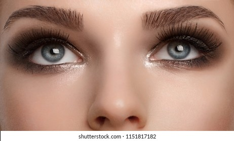 Closeup female eyes with bright make-up, great shapes brows, extreme long eyelashes. Celebrate makeup, luxury eyeshadows. Macro of beautiful eye. Good vision