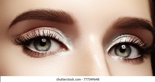 Closeup female eyes with bright make-up, great shapes brows, extreme long eyelashes. Celebrate makeup, luxury eyeshadows. Macro of beautiful eye. Good vision
