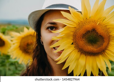 Close-up female face, half of female face covered with a sunflower flower, a woman looking at the frame.