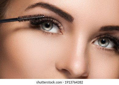 Close-up of female face and mascara wand for maximum volume of artificial eyelashes - Shutterstock ID 1913764282